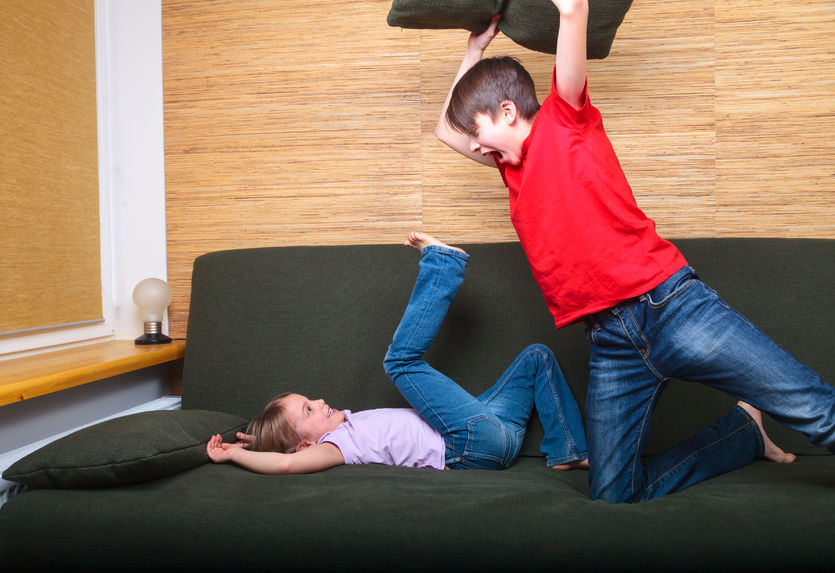 51293605 - brother and sister  wearing casual clothes  playing on a green sofa at home fighting with pillows